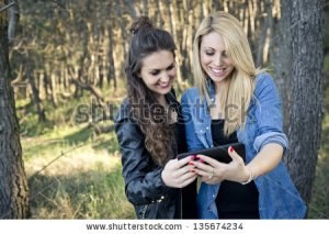 stock-photo-two-young-woman-with-tablet-at-the-park-135674234