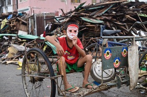 Tacloban, Philippines: A boy with a Santa Claus mask sits on a pedicab amon